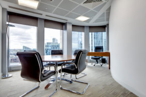 """Small modern office boardroom and meeting room interior with desks, chairs and cityscape view"""